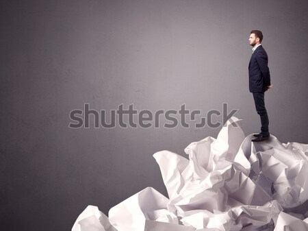 Businessman standing on crumpled paper Stock photo © ra2studio