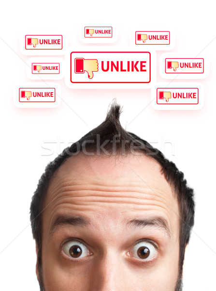 Young man with UNLIKE sign over his head  Stock photo © ra2studio