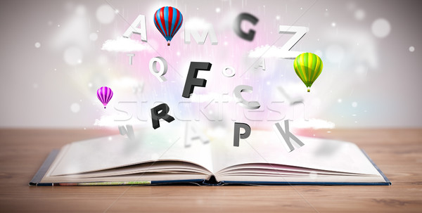 Stock photo: Open book with flying 3d letters on concrete background