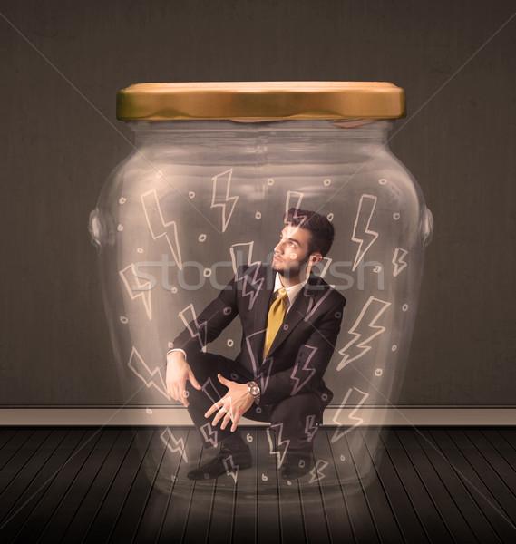 Businessman inside a glass jar with lightning drawings concept Stock photo © ra2studio