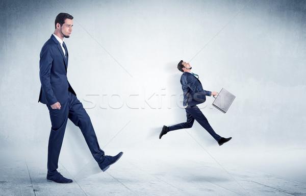 Big businessman kicking small businessman Stock photo © ra2studio