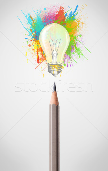 Pencil close-up with colored paint splashes and lightbulb Stock photo © ra2studio