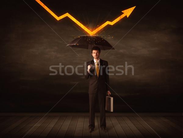Businessman standing with umbrella keeping orange arrow  Stock photo © ra2studio