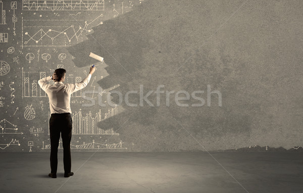 Salesman painting over charts on wall Stock photo © ra2studio