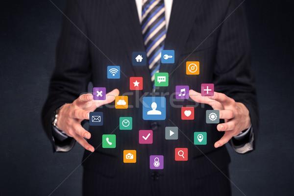 Businessman holding colorful applications Stock photo © ra2studio