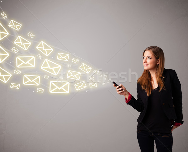 Stock photo: attractive young lady holding a phone with message icons