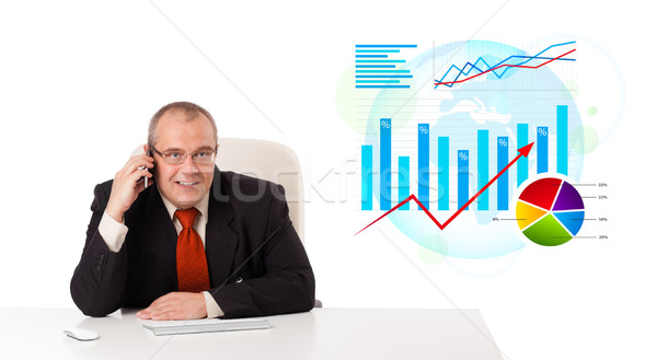Businessman sitting at desk with statistics and making a phone call, isolated on white Stock photo © ra2studio