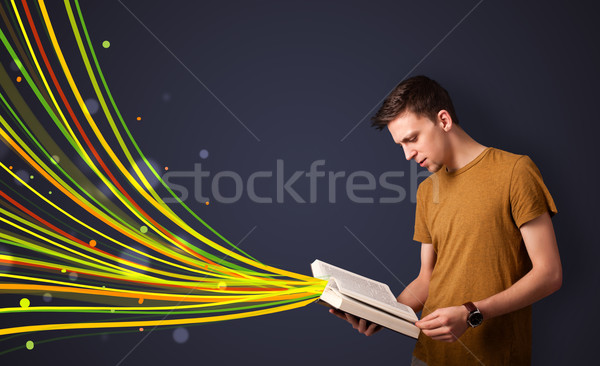 Young man reading a book while colorful lines are coming out of the book Stock photo © ra2studio