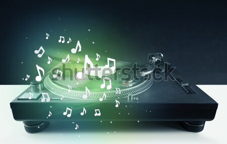 Turntable playing music with audio notes glowing Stock photo © ra2studio