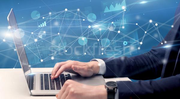 Mão datilografia laptop relatório gráficos em torno de Foto stock © ra2studio