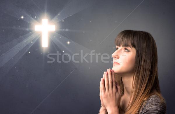 Modląc młoda dziewczyna młoda kobieta szary błyszczący krzyż Zdjęcia stock © ra2studio