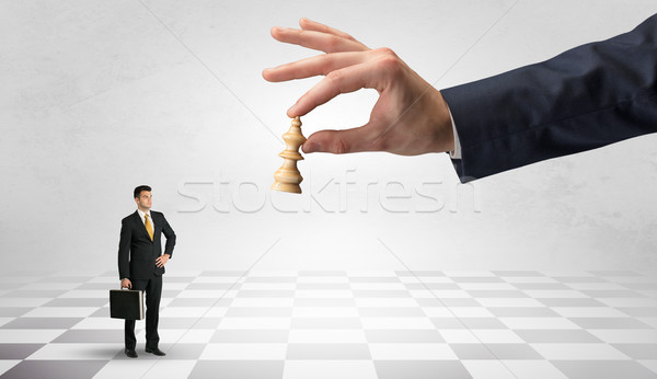 Businessman fighting against big chessman on a big hand Stock photo © ra2studio