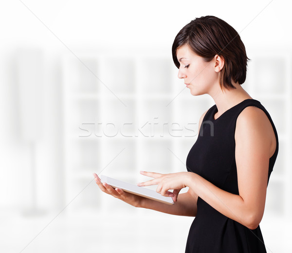 Stock photo: Young woman looking at modern tablet
