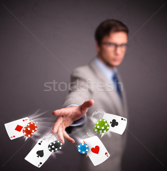 Young man playing with poker cards and chips Stock photo © ra2studio
