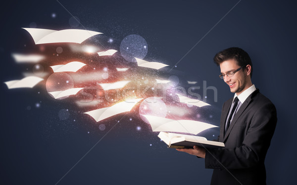 Young guy reading a book with flying sheets coming out of the book, magical reading concept Stock photo © ra2studio