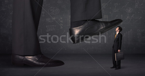 Huge leg stepping on a tiny businnessman concept Stock photo © ra2studio