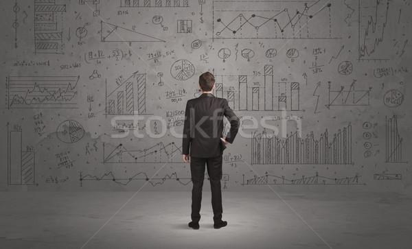 Salesman with business charts on wall Stock photo © ra2studio