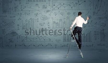 Man on ladder drawing charts Stock photo © ra2studio