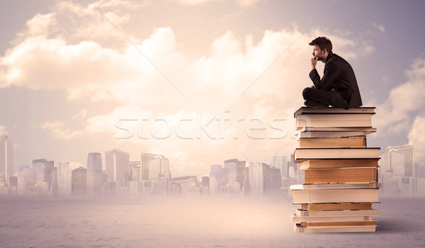 Man sitting on pile of books above city Stock photo © ra2studio
