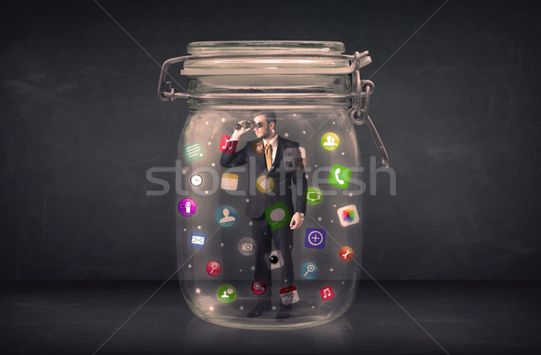 Businessman captured in a glass jar with colourful app icons con Stock photo © ra2studio