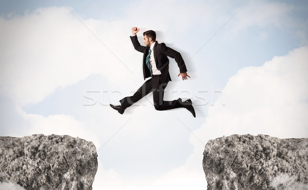 Funny business man jumping over rocks with gap Stock photo © ra2studio