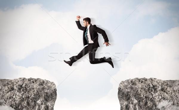 Engraçado homem de negócios saltando rochas lacuna céu Foto stock © ra2studio