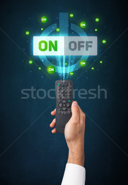 Stock photo: Hand with remote control and on-off signals