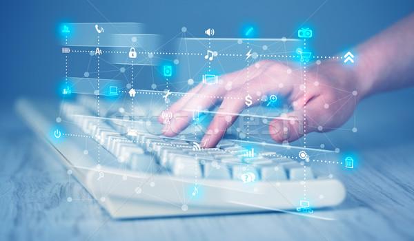 Hand pressing keyboard with high tech media icons Stock photo © ra2studio