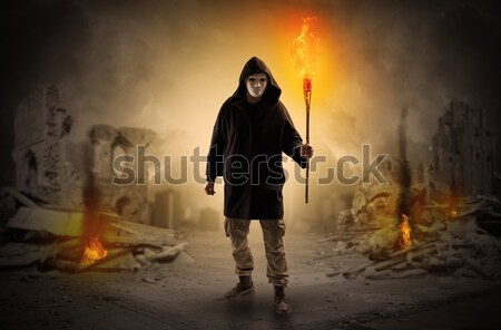 Man coming with burning flambeau at a catastrophe scene concept Stock photo © ra2studio