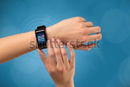 Female hand wearing and pressing smartwatch Stock photo © ra2studio