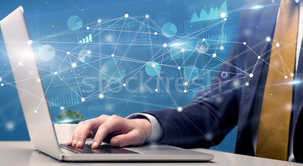 Hand typing on laptop with linked report and charts around Stock photo © ra2studio