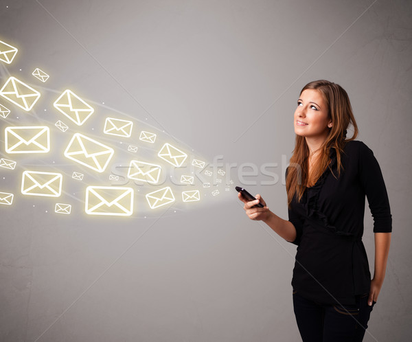 attractive young lady holding a phone with message icons Stock photo © ra2studio