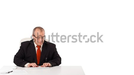 businessman sitting at desk and typing on keyboard with copy scape, isolated on white Stock photo © ra2studio