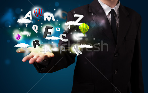 Young businessman presenting magical clouds with letters and bal Stock photo © ra2studio