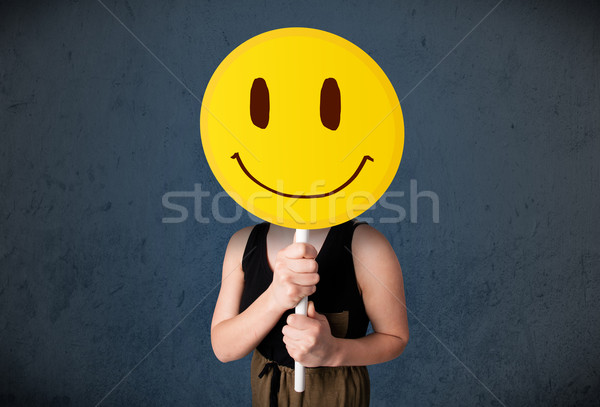 Young woman holding a smiley face emoticon Stock photo © ra2studio