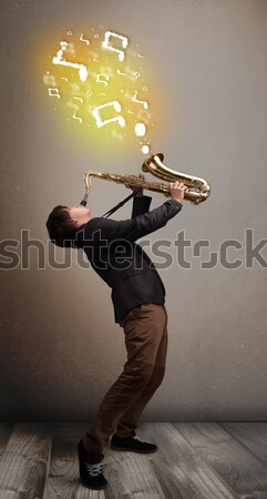 Handsome musician playing on saxophone with musical notes Stock photo © ra2studio