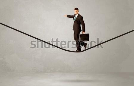 Salesman walking on rope in grey space Stock photo © ra2studio