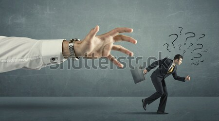 Businessman with question marks running away from a big hand  Stock photo © ra2studio
