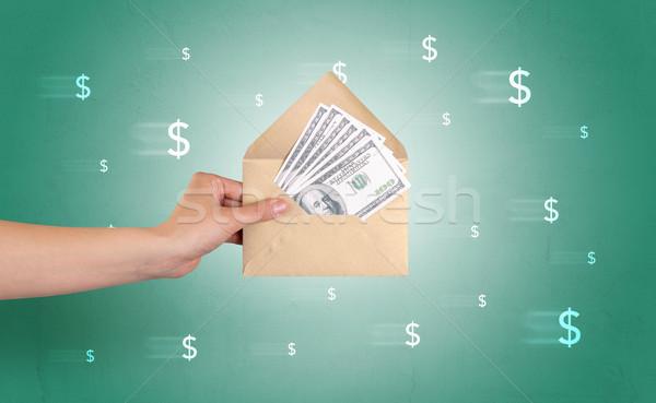 Hand holding envelope with symbols around Stock photo © ra2studio