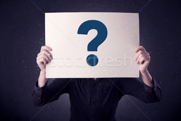 Businessman holding paper with question marks Stock photo © ra2studio
