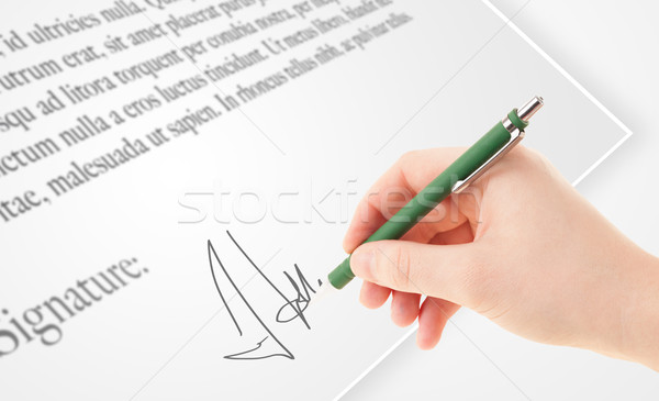 Hand writing personal signature on a paper form Stock photo © ra2studio