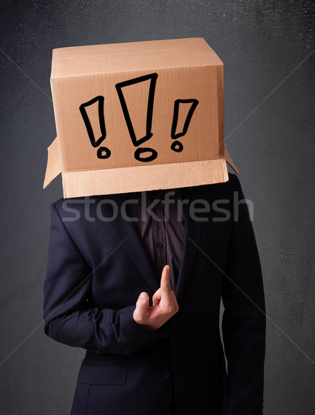Young man gesturing with a cardboard box on his head with exclam Stock photo © ra2studio