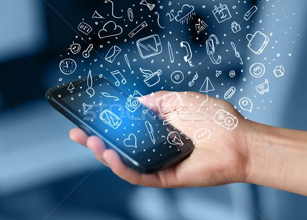 Kéz tart okostelefon kézzel rajzolt média ikonok Stock fotó © ra2studio