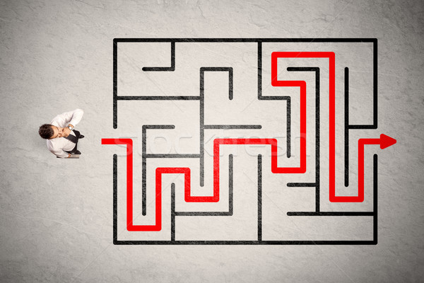 Lost businessman found the way in maze with red arrow Stock photo © ra2studio