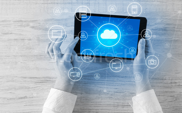 Stock photo: Hand using tablet with centralized cloud computing system concep