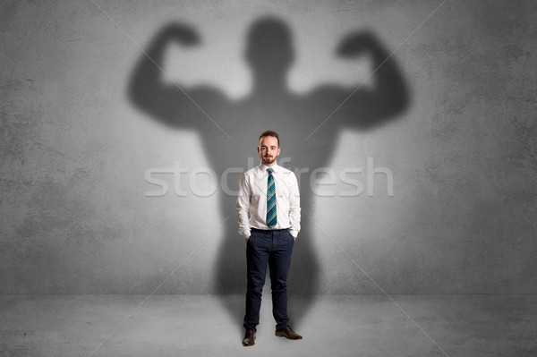 Businessman with muscular shade behind his back Stock photo © ra2studio