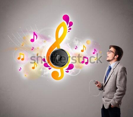 Fiatalember énekel zenét hallgat hangjegyek ki száj Stock fotó © ra2studio