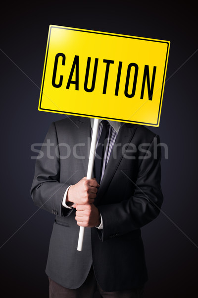 üzletember tart vigyázat felirat áll citromsárga Stock fotó © ra2studio