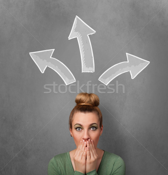 Young woman thinking with arrows above her head Stock photo © ra2studio