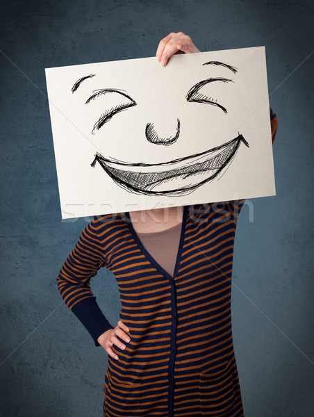 Woman with drawed smiley face on a paper in front of her head Stock photo © ra2studio